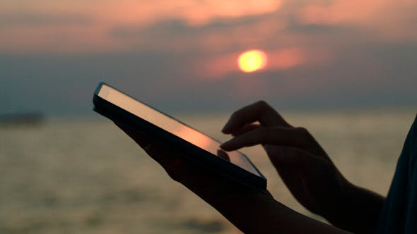 Thumbnail for Using Touchpad On The Beach At Sunset