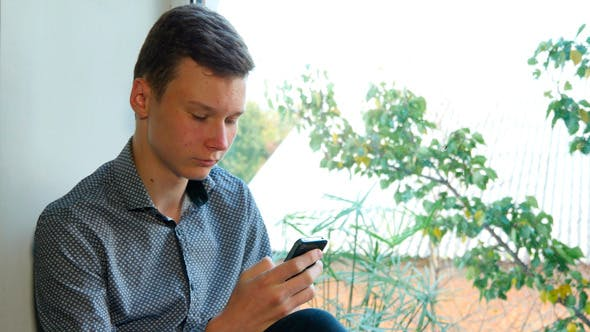 Thumbnail for Teenager Sitting By A Window Using His Smartphone