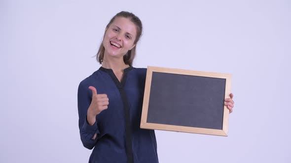 Thumbnail for Happy Young Beautiful Businesswoman Holding Blackboard and Giving Thumbs Up