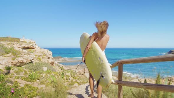 Thumbnail for Rear View of Attractive Surfer Girl, Walking on Beach with Surfboard