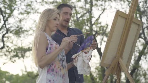 Creative Couple Painting Picture Outdoors Together. Portrait of Loving Inspired Caucasian Man and