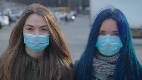 Cover Image for Close-up Faces of Two Young Women in Protective Masks Looking at Camera at the Background of Busy