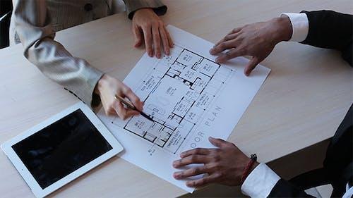 Immobilienmakler diskutieren mit einem Kunden