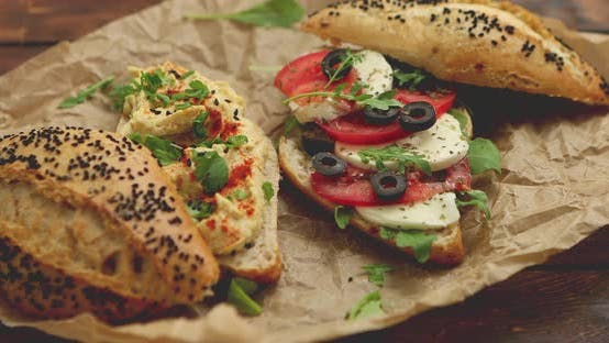 Thumbnail for Two Delicious Sandwiches with Hummus, Tomato, Mozarella Cheese, Herbs and Olives