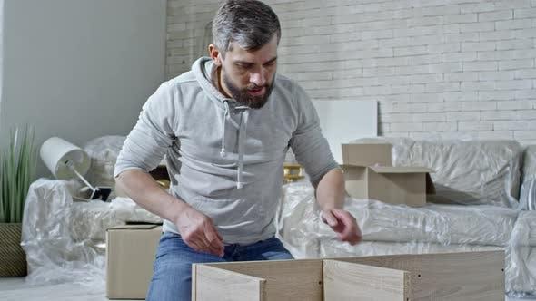 Thumbnail for Man Assembling Wooden Furniture