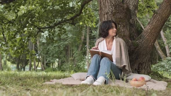 Junge Frau schreibt in der Molkerei im Freien