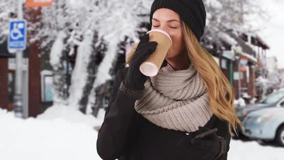 Thumbnail for Millennial girl drinking coffee outside in the snow rolling her eyes at her phone