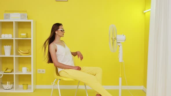 Junge Frau entspannt sich vor dem elektrischen Ventilator