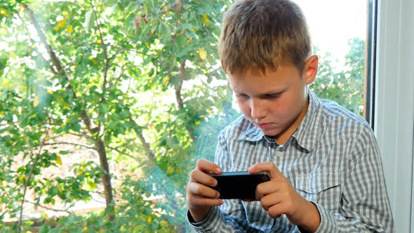 Thumbnail for Boy Sitting By A Window Using His Smartphone