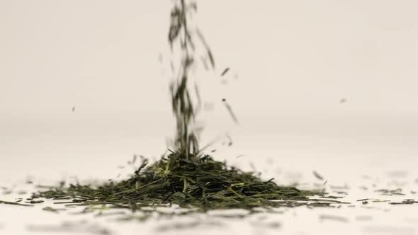 Macro shot of tea leaves fall on a pile of a green tea