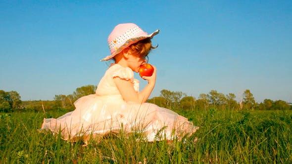 Thumbnail for Little Girl Eating Apple On Meadow