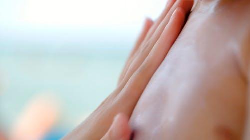 Mother Applying Sunscreen On Sons Skin