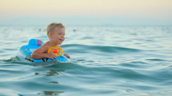 Thumbnail for Boy With Rubber Ring Swimming In Sea