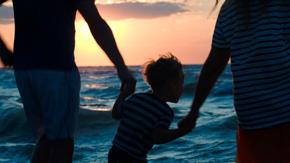 Thumbnail for Happy Family Of Three Dancing By Sea At Sunset