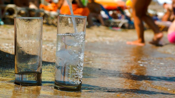 Thumbnail for Pouring Water Into Two Glasses On Beach