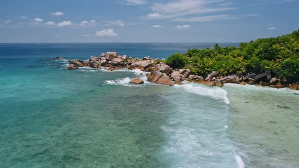 Thumbnail for Aerial Drone View of Remote Secluded Beach with Granite Boulders, Ocean Waves and Palm Trees