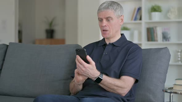 Thumbnail for Middle Aged Businessman Celebrating Success on Smartphone on Sofa