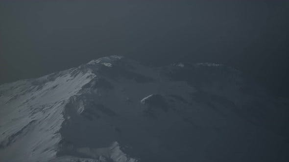 Dramatic Dark Rocky Mountain with Patches of Snow in Storm