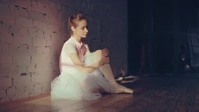 Ballerina Sitting Against the Wall Resting