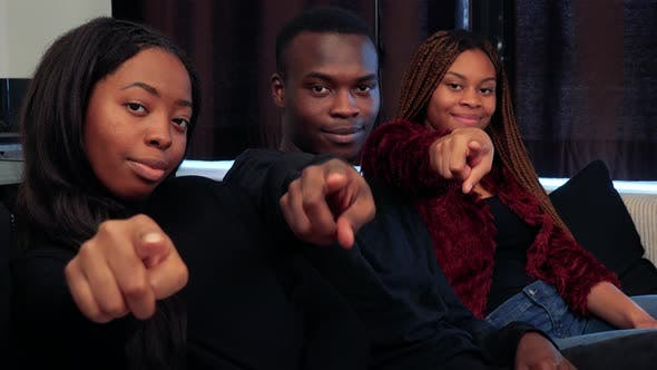 Three African Friends Point To Camera with Finger and Smile in Living Room