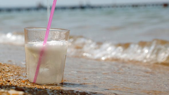 Thumbnail for Pouring Fizzy Drink Into Glass On The Sand
