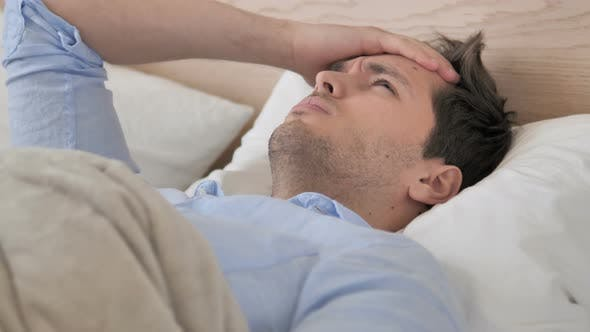 Thumbnail for Angespannter junger Mann mit Kopfschmerzen im Bett liegend