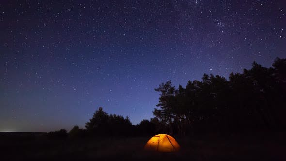 Thumbnail for Orange Iluminated Tent in the Forest Under the Starry Sky. Timelapse