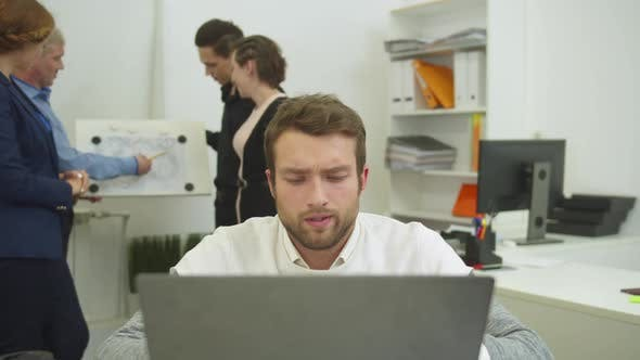 Thumbnail for Man Working at the Laptop, His Workmates Discuss Scheme of Apartement
