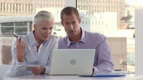 Thumbnail for Two Businesspeople Using Laptop in Office