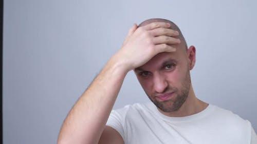 A Bald Man Puts on a Wig