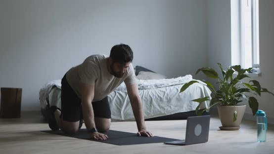 Thumbnail for Bearded Man Exercising on Mat with Laptop at Home
