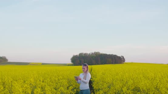 Young Farmer Using Digital Tablet at Oilseed Rape Field