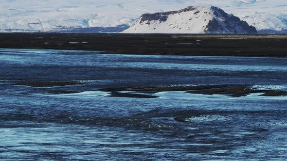 Thumbnail for Black Sand Beach with Snow Covered Mountains in the Background