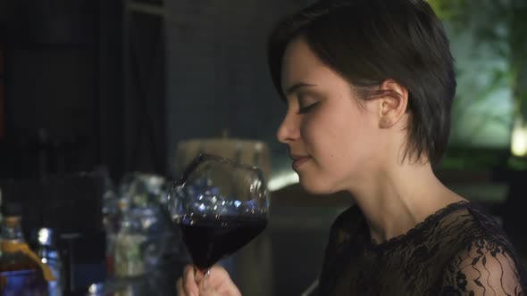 Cropped Shot of a Gorgeous Brunette Enjoying Drinking Wine at the Bar Smiling To the Camera
