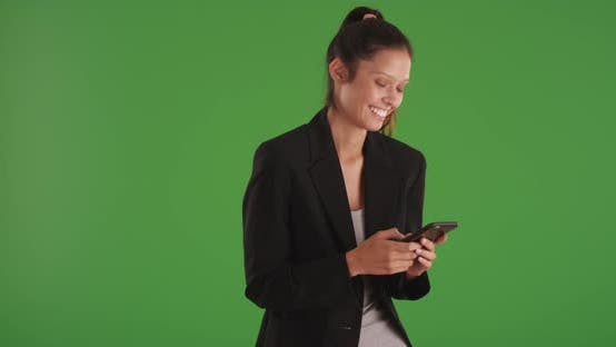 Thumbnail for Happy businesswoman reading text messages on smartphone on greenscreen