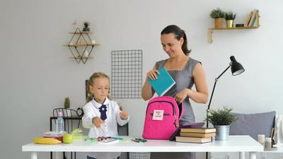 Little Girl with Mom Preparing School Backpack