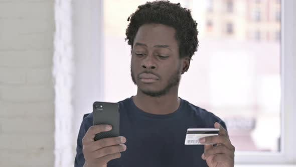 Thumbnail for Portrait of Young African American Man Making Online Payment on Smartphone
