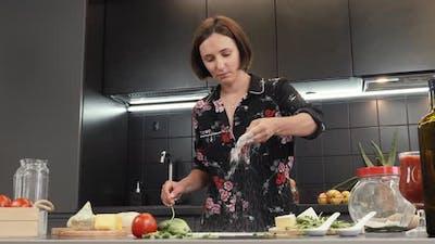 Woman sprinkling flour on table