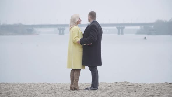 Blond Caucasian Woman Hugging Loving Man on Riverbank