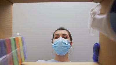 Woman in Mask Taking Cleaning Supplies From Box
