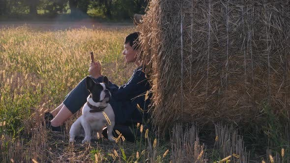 Thumbnail for Young Woman Sitting at the Meadow with French Bulldog
