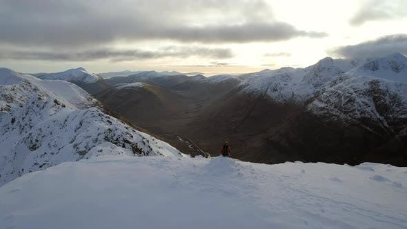 Mountaineer on the Summit of a Snowy Mountain