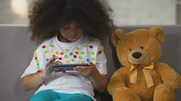 Funny Black-Haired Girl Sitting on Sofa and Playing Game on Smartphone, Rest