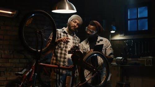 Two Mechanic Talking in a Workshop