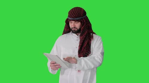 Sheikh Using Digital Tablet and Walking on a Green Screen, Chroma Key.
