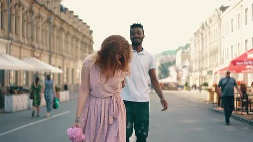 Young Happy Woman Leads Her Boyfriend's Hand Along City Street