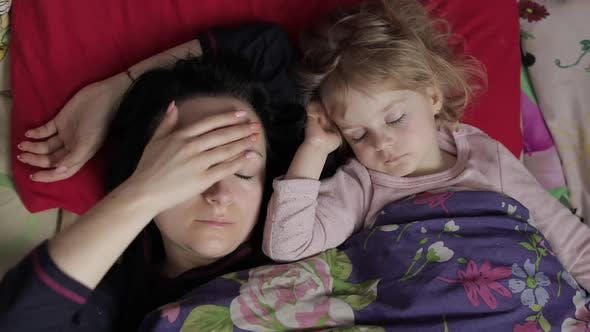 Sleepy Young Woman with Her Baby Does Not Want To Wake Up in the Morning