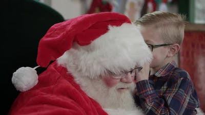 Boy whispers into Santa's ear