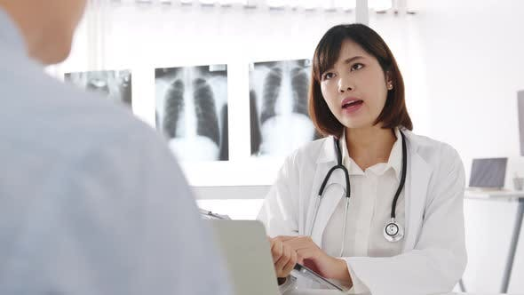 Young Asia female doctor using clipboard is discuss results or symptoms with male patient.