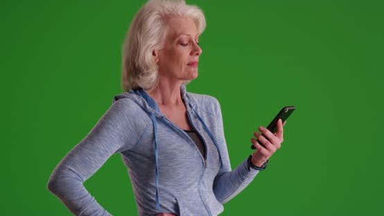 Thumbnail for Mature woman in her 50s texting on smart phone on greenscreen